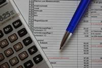 Foto; Taschenrechner, Kalkulationstabelle und Kugelschreiber