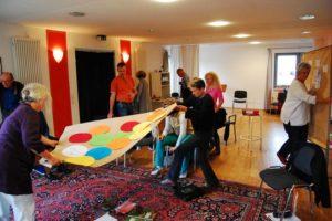 Foto der Gruppe in einem Workshop zur Weiterentwicklung des Wohnprojektes; Gruppenarbeit; Stellwände mit Ideen, aufgeschrieben auf bunten Denkzetteln, kreative Arbeitsmethoden