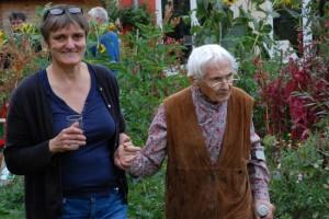 Foto; zwei Frauen spazieren im Garten, die jüngere Frau reicht der älteren Frau die Hand als Stütze beim Laufen