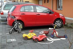 Foto; Parkplatz, im Hintergrund ein roter Kleinwagen, im Vordergrund ein Rollator, ein Dreirad, zwei Bobby-Cars und ein Kinderroller