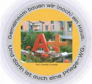 """Emblem; in der Mitte des Emblems ein Foto; darauf der Großbuchstabe A und das Zeichen für Plus aus Holz in einem blühenden Garten; die Rechte am Foto hat Charlotte Schaeder; der Text, kreisförmig um das Foto gelegt, lautet: """"Gemeinsam bauen wir (noch) ein Haus. Und darin ist auch eine Pflege-WG."""""""